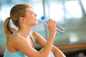 Profile of beautiful woman going to drink some water from plastic bottle after workout